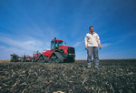 young farmer in front of seeding equipment, near Anola, Manitoba, Canada