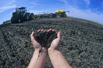 hands holding soil with seeding equipment in the background, Manitoba, Canada