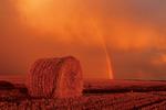 round barley straw bale, sky with rainbow and cumulonimbus clouds, Tiger Hills, Manitoba