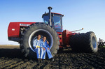 mother/daughter sitting on tractor tire, Manitoba, Canada