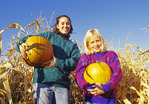 two girls holding pumpkins near a corn field, near St. Adolphe, Manitoba, Canada