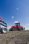 a farmer walks toward his Quadtrac tractor and air till seeder, near Lorette, Manitoba, Canada
