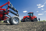 a farmer walks toward his Quadtrac tractor and air till seeder, near Lorette, Manitoba, Canada