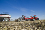 moving tractor and and air till seeder planting soybeans in grain stubble, near Dugald, Manitoba, Canada