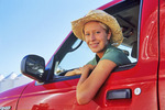 a farm girl in a red pick-up truck with grain storage bins in the background,near Dugald, Manitoba, Canada