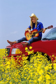 16 year old  on truck with guitar  (canola field), near St. Leon, Manitoba, Canada