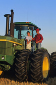 father and son on the front of a tractor, near Carey, Manitoba, Canada