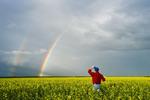 man in bloom stage canola field , near Anola,  Manitoba, Canada