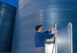 a man turns on an aeration fan on a  grain storage bins in the evening,near Dugald, Manitoba, Canada