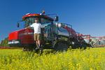 farmer on high clearance sprayer in canola field near Dugald, Manitoba, Canada