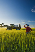 a man looks out over a barley field next to a high clearance sprayer that was applying fungicide, near Holland, Manitoba, Canada