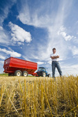 a farmer standing in oat stubble in front of a tractor and grain wagon during the harvest, near Dugald, Manitoba, Canada