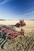 moving tractor and and air till seeder planting winter wheat in a zero till canola stubble field, Lorette, Manitoba, Canada