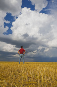 a man looks out over a harvested oat field with a cumulonimbus cloud buildup in the background, near Dugald, Manitoba, Canada