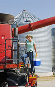 a  farm girl on the deck of a combine in a farmyard prepares for a day of harvesting, near Dugald,  Manitoba, Canada