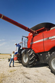a farm girl brings lunch to her father on the deck of a combine during the harvest, near Dugald,  Manitoba, Canada