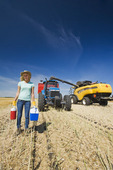 a farm girl standing in oat stubble in front of a tractor, grain wagon and combine during the harvest, near Dugald, Manitoba, Canada