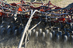 close-up of packers on an air till seeder planting winter wheat in a zero till canola stubble field, Lorette, Manitoba, Canada