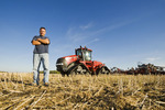 a farmer in field, tractor and and air till seeder in the background used to plant winter wheat in a zero till canola stubble field, Lorette, Manitoba, Canada
