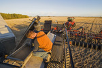 young farmer loading a seeding tank with winter wheat seed and fertilizer, near Lorette, Manitoba, Canada