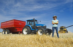 a farm girl standing in oat stubble in front of a tractor and grain wagon during the harvest, near Dugald, Manitoba, Canada