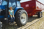 a farm girl on the deck of a tractor with grain wagon during the harvest, near Dugald,  Manitoba, Canada