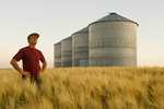 a man in a maturing barley field with grain bins in the background, near Carey, Manitoba, Canada