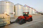  a tractor and grain wagon loaded with wheat passes grain storage bins during the harvest, near Lorette,  Manitoba, Canada