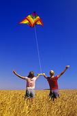 two girls fly a kite in a spring wheat field near Winnipeg, Manitoba, Canada