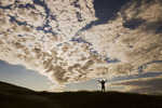 a man with arms outstretched looks out over a sky filled with clouds, near Ponteix, Saskatchewan, Canada