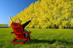 a man sits in a chair at the edge of a hay field with a shelterbelt in autumn colours in the background near Dufresne, Manitoba, Canada