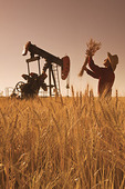 a man checks hatvest ready wheat as an oil pumpjack works in the background, near Sinclair, Manitoba, Canada