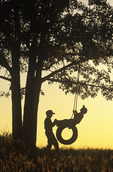 children playing on tire swing , Manitoba , Canada