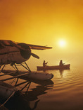 couple canoeing next to float plane, along Red River, Manitoba, Canada