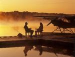 couple relaxing on float plane dock, along Red River, Manitoba, Canada