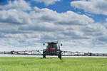 a high clearance sprayer gives a chemical application of fungicide to wheat, near Dugald, Manitoba, Canada