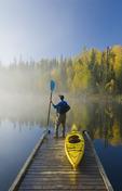 a man on dock with kayak, Dickens Lake,  Saskatchewan, Canada