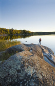 hiker on rock, Devil Lake,  Northern Saskatchewan, Canada