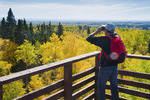 a hiker admires the view from Baldy Mountain, highest point in Manitoba,  Duck Mountain Provincial Park, Manitoba, Canada