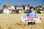 a farmer holding a sign, looks out over a mature winter wheat field  next to urban sprawl,  Winnipeg , Manitoba, Canada