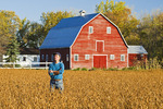 man in mature soybean field with red barn in the background, Grande Pointe,  Manitoba, Canada