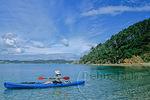 Kayaker paddles off Roberton Island, Bay of Islands, New Zealand