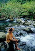 Hiker relaxes by stream in Waihee Valley