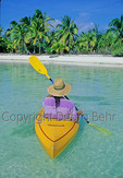 Kayaker in the Aitutaki Lagoon paddles toward a motu
