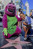Boy and street performer dressed as Barney on Hollywood Boulevard near Highland