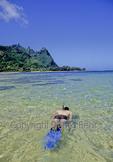 Snorkeler off Tunnels Beach on Kauai, with Bali Hai in background