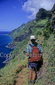 Hiker on narrow stretch of the Kalalau Trail sees the Na Pali Coast on Kauai