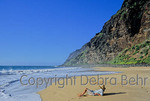Tourist relaxes on golden sand at Polihale State Beach
