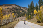 Bicyclist pedals by autumn colors along old Vail Pass road in Colorado