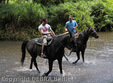 Horseback guide with Naalapa Stables, right, chats with rider exploring jungly Waipio Valley